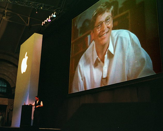 FILE - In this Aug. 6, 1997, file photo, Apple co-founder Steve Jobs, background left, stands at a podium as Bill Gates, chief executive of Microsoft Corp., appears on a video screen during Jobs' addr