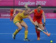 Jodie Schulz of Australia (L) fights for the ball with Zhao Yudiao of China during their women&#39;s field hockey match at the Riverbank Arena in London. Three-times Olympic champions Australia finished fifth in the women&#39;s hockey tournament after chiselling out a 2-0 win over China with with a hard-fought but sometimes rather toothless performance