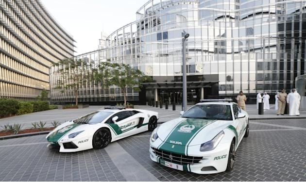 A picture taken on April 25, 2013 shows Lamborghini and Ferrari police vehicles at the foot of the Burj Khalifa tower  in the Gulf emirate of Dubai. Two weeks after introducing the Lamborghini police