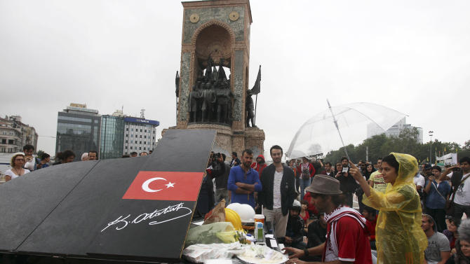 A musician plays the piano as a protester holds an umbrella to protect him from the rain under the monument of Mustafa Kemal Ataturk, founder of the modern Turkey, at Taksim Square in Istanbul Friday, June 14, 2013. Five people, including a police officer, have died and over 5,000 protesters and 600 police have been reported injured in clashes around the country. A meeting between Prime Minister Recep Tayyip Erdogan and representatives of anti-government protesters ended early Friday without a clear resolution on how to end the occupation of a central Istanbul park that has become a flashpoint for the largest political crisis of his 10-year rule. (AP Photo/Thanassis Stavrakis)