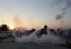 An anti-government protester throws tear-gas canister, initially fired by riot-police, back at them during clashes after funeral of Ali Khalil in Bani Jamra