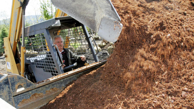 """In this May 17, 2012 photo, Richard Lowe loads a truck with mulch in Morrisville, Vt. Nursery owners and landscapers around Vermont have been getting big bills from the state recently for unpaid sales taxes on products like bark mulch and soil additives that many thought had an agricultural exemption from the 6 percent levy. Some are complaining that they were caught unaware of a change in the tax code made six years ago. """"You don't just change the taxes and laws and not tell somebody,"""" said Lowe, owner of Green Mountain Landscaping in Morrisville, who is fighting $18,000 in bills for back taxes. (AP Photo/Toby Talbot)"""