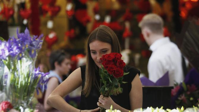 A worker prepares a red roses bouquet to be sold as a Valentine's day special at a flowers boutique in Sydney