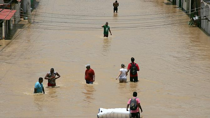Residents wade through a neighbourhood flooded by the Acre river, which continues to rise from weeks of heavy rainfall in the region including northern Bolivia, in Rio Branco
