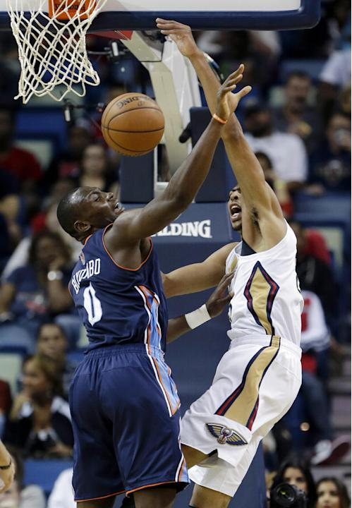 New Orleans Pelicans forward Anthony Davis, right, vies for a loose ball against Charlotte Bobcats forward Bismack Biyombo (0) in the first half of an NBA basketball game in New Orleans, Saturday, Nov
