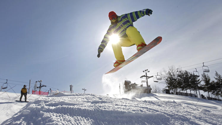 FILE - In this Jan. 24, 2013 file photo, Mason Bemiller, 17, from Northridge High School in Middlebury, Ind., snowboards through the terrain park at Swiss Valley ski area in Jones, Mich. The lack of snow in some places, and in even places with snow that are getting less than usual, illustrates the increasingly fickle nature of winter in the Midwest, where dry, mild weather is making life difficult for businesses that rely on abundant snow. (AP Photo/Kalamazoo Gazette-MLive Media Group, Mark Bugnaski) ALL LOCAL TV OUT; LOCAL TV INTERNET OUT
