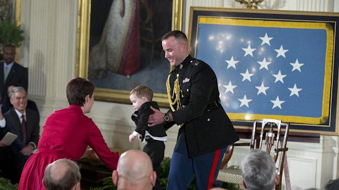A White House military aide carries Colin Romesha, son of retired Staff Sgt. Clinton Romesha, off stage back to his seat for a ceremony to award Romesha the Medal of Honor, Monday, Feb. 11, 2013, in the East Room of the White House in Washington.  Romesha's leadership during a daylong attack by hundreds of fighters on Combat Outpost Keating in Afghanistan led to award. (AP Photo/ Evan Vucci)