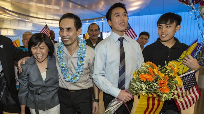 Human rights activist  Nguyen Quoc Quan, 2nd from left, is welcomed by his wife Huong Mai Ngo, left, sons Khoa, 2nd right, 20, and Tri, 19, after his arrival at the Los Angeles International Airport from Vietnam on Wednesday, Jan. 30, 2013, in Los Angeles.  Quan has been released after being detained since April 17, 2012 in Ho Chi Minh City, Vietnam. (AP Photo/Ringo H.W. Chiu)