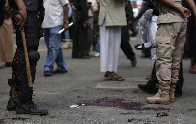 A Yemeni soldier, left, stands next to the blood of police cadets who were killed in a suicide bomb attack at a police academy in Sanaa, Yemen, Wednesday, July 11, 2012. A suicide bomber threw himself into a crowd of Yemeni police cadets leaving their academy on Wednesday and detonated his explosives, killing several people, a security official said.(AP Photo/Hani Mohammed)