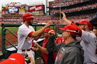 Matt Carpenter (L) of the St. Louis Cardinals is congratulated at the dugout by Mark McGwire and pitcher Chris Carpenter after Matt Carpenter hits a two-run home run in the third inning against the San Francisco Giants, in game three of their National League Championship Series at Busch Stadium in St Louis, Missouri. The Cardinals won the game 3-1, taking the series lead, 2-1