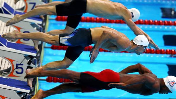 Michael Phelps (C) dives of off the starting block as he competes in preliminary heat 13 of the Men's 100 m Butterfly during Day Six of the 2012 U.S. Olympic Swimming Team Trials at CenturyLink Center on June 30, 2012 in Omaha, Nebraska. (Photo by Al Bello/Getty Images)