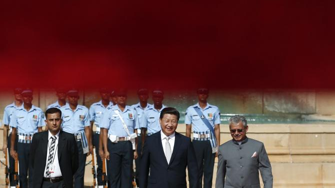 China's President Xi walks on the red carpet after inspecting a guard of honour during his ceremonial reception in New Delhi