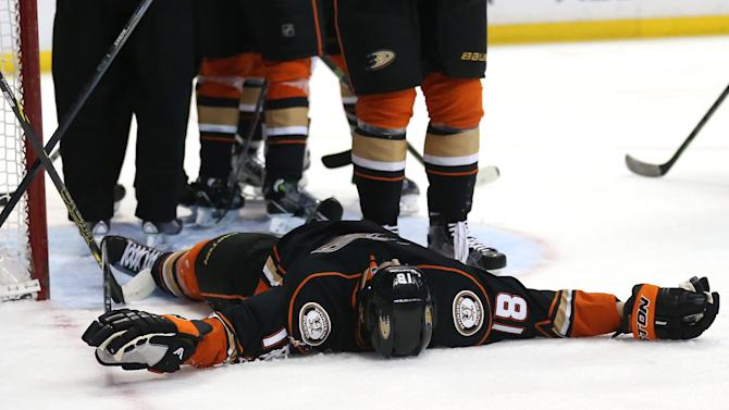 Tim Jackman of the Anaheim Ducks lays motionless on the ice after running into John Scott of the San Jose Sharks at Honda Center on December 22, 2014 in Anaheim, California