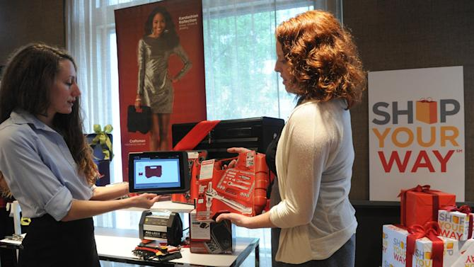 IMAGE DISTRIBUTED FOR SEARS AND KMART - Torie Johnson, left, product manager, Sears, showcases their new mobile checkout  technology that enables faster service for customers in stores, during the Sears and Kmart holiday media event, Thursday, Oct. 4, 2012, in New York.   (Diane Bondareff/Invision for Sears and Kmart/AP Images)