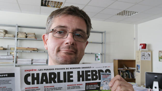 """Publishing director of the satyric weekly Charlie Hebdo, Charb, displays the front page of the newspaper as he poses for photographers in Paris, Wednesday, Sept. 19, 2012. Police took up positions outside the Paris offices of the satirical French weekly that published crude caricatures of the Prophet Muhammad on Wednesday that ridicule the film and the furor surrounding it. The provocative weekly, Charlie Hebdo, was firebombed last year after it released a special edition that portrayed the Prophet Muhammad as a """"guest editor"""" and took aim at radical Islam. (AP Photo/MIchel Euler)"""