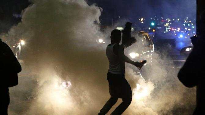 Protesters run when the police shoot tear gas in Ferguson, Mo., Sunday, Aug. 17, 2014. Protests over the killing of 18-year-old Michael Brown by a white police officer have entered their second week. (AP Photo/St. Louis Post-Dispatch, J.B. Forbes)