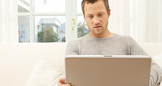 Man sitting with laptop copyright MJTH/Shutterstock.com