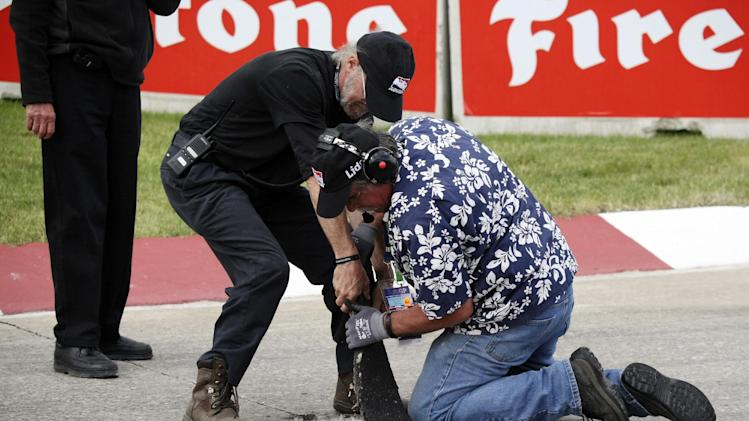 Track officials pull up asphalt on Turn 6 during IndyCar's Detroit Grand Prix auto race on Belle Isle in Detroit, Sunday, June 3, 2012. (AP Photo/Bob Brodbeck)
