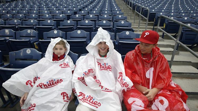 From left, brothers Colin, 9, Aidan, 12, and Michael Daniels, of McKinney, Texas, wait in their Philadelphia Phillies rain ponchos before a spring exhibition baseball game between the Phillies and the Baltimore Orioles in Clearwater, Fla., Monday, March 17, 2014