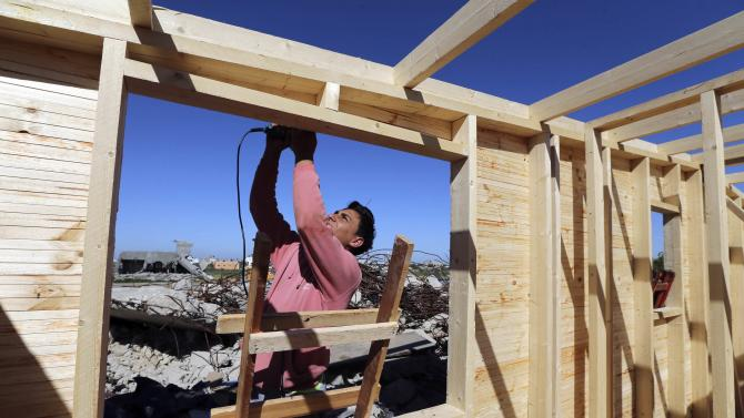 A worker participates in efforts to build wooden shelters for Palestinians whose houses were destroyed by what witnesses said was Israeli shelling during a 50- day-war last summer, east of Khan Younis in the southern Gaza Strip