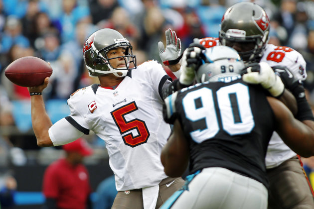 Tampa Bay Buccaneers quarterback Josh Freeman (5) throws a pass under pressure from Carolina Panthers' Frank Alexander (90) during the first half of an NFL football game in Charlotte, N.C., Sunday