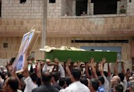 A handout picture released by the Syrian opposition's Shaam News Network shows Syrians lifting the coffin of Ahmad Msalmeh and Mohammed al-Najjar during their joint funeral in Daraa
