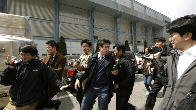 A South Korean worker, fifth from left, who arrived with boxes of products, seen at left, from North Korea's Kaesong is questioned by media upon his arrival at the customs, immigration and quarantine office near the border village of Panmunjom, which has separated the two Koreas since the Korean War, in Paju, north of Seoul, South Korea, Tuesday, April 9, 2013. North Korean workers didn't show up for work at the Kaesong industrial complex, a jointly run factory complex with South Korea on Tuesday, a day after Pyongyang suspended operations at the last remaining major economic link between rivals locked in an increasingly hostile relationship. (AP Photo/Lee Jin-man)