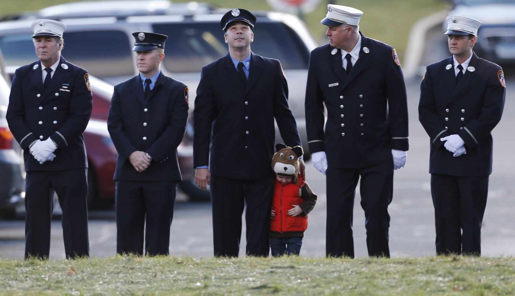 A child lines up with firefighters outside the funeral for school shooting victim Daniel Gerard Barden,at St. Rose of Lima Catholic Church in Newtown, Conn., Wednesday, Dec. 19, 2012.