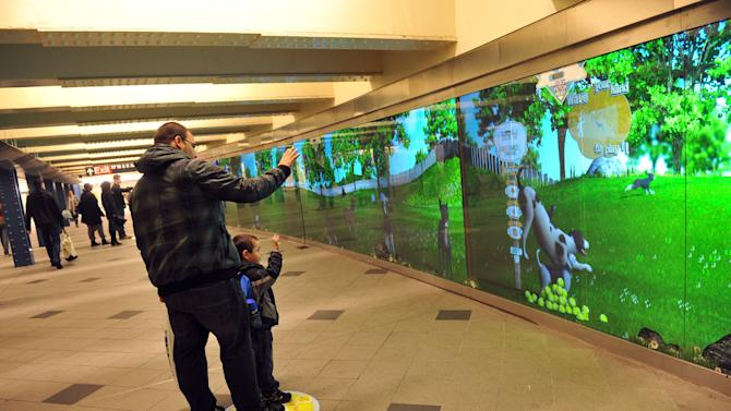 COMMERCIAL IMAGE - In this photograph taken by AP Images for Beneful, New Yorkers in the Columbus Circle subway station play a game of fetch with virtual dogs on a state-of-the-art interactive billboard from Beneful brand dog food, Tuesday, May 1, 2012.  The billboard, designed to inspire commuters to PLAY, will be in the Columbus Circle station during the month of May. Visit Facebook.com/Beneful to learn more. (Diane Bondareff/AP Images for Beneful)