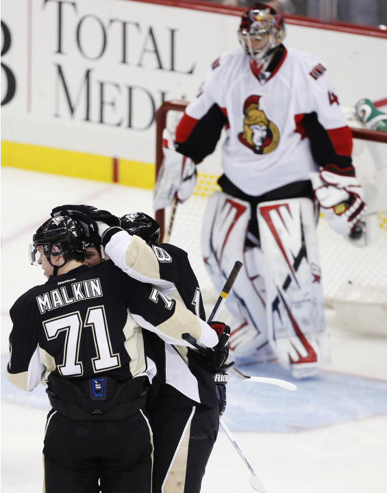 Ottawa Senators goalie Anderson watches as Pittsburgh Penguins' Malkin congratulates teammate Neal on his goal in their NHL hockey game in Pittsburgh