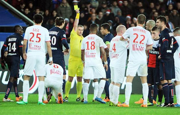. Paris (France), 22/12/2013.- PSG striker Zlatan Ibrahimovic (L) is shown the yellow card by referee Fredy Fautrel during the French Ligue 1 soccer match between Paris Saint Germain and Lille OSC at