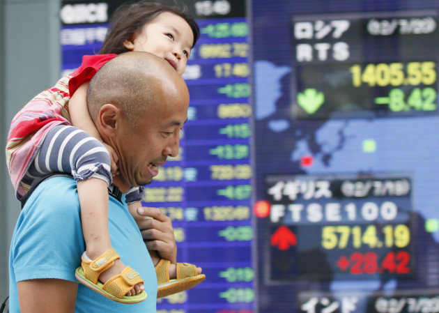 A man carries a child on his shoulders near an electronic stock board outside a securities firm in Tokyo, Friday, July 20, 2012. Asian stock markets wavered Friday as weak U.S. data kept sentiment in check despite continued hopes for new stimulus measures in major economies. Japan's Nikkei 225 was down 0.9 percent at 8,717.60. (AP Photo/Koji Sasahara)