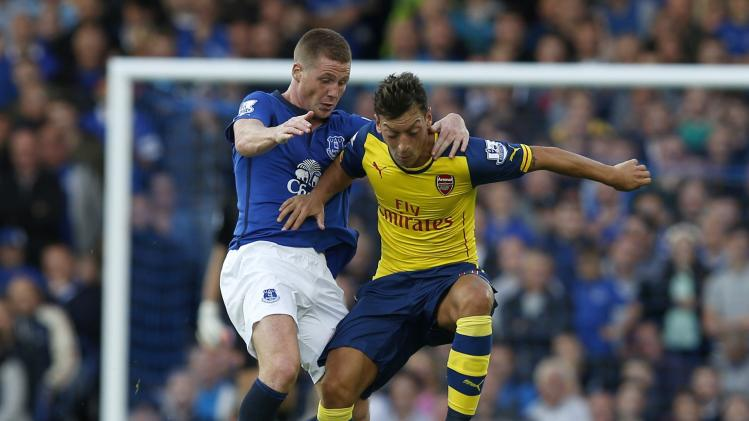 Everton's McCarthy challenges Arsenal's Ozil during their English Premier League soccer match at Goodison Park in Liverpool