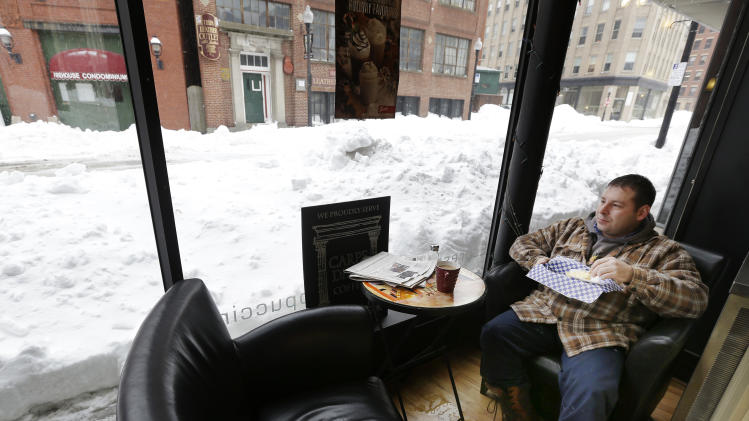 Matt Church enjoys his breakfast at a coffee shop in downtown Haverhill, Mass., Monday, Feb. 11, 2013. Beleaguered Massachusetts residents returned to work on Monday for the first time since the weekend blizzard, crawling along narrow snow-covered secondary roads and being greeted by a new wintry mix of sleet and freezing rain. (AP Photo/Elise Amendola)