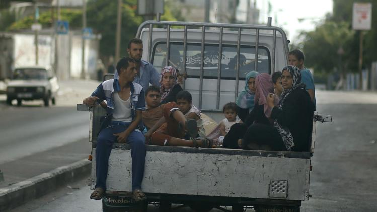 Palestinians, who fled their homes that are adjacent to the border with Israel, ride in a truck as they make their way to stay in a United Nations-run school in Gaza City