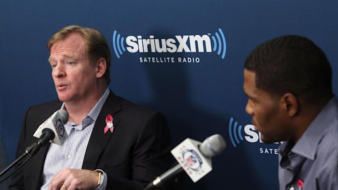 NFL Commissioner Roger Goodell, left, talks while former New York Giants defensive end Michael Strahan, right, and football fans listen during a Sirius XM Town Hall event in New York, Monday, Oct. 22, 2012. (AP Photo/Seth Wenig)