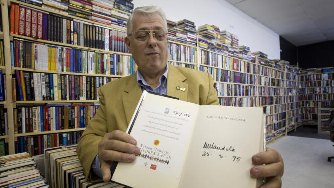 In this Friday, Oct. 19, 2012 photo, memorabilia collector Ken Kallin poses with a copy of his autographed Nelson Mandela book from his collection in Oakland Park, Fla. Three decades ago, Kallin began amassing 120,000 pieces in a memorabilia collection that includes photographs signed by Muhammad Ali and Neil Armstrong along with rare books and trading cards. By the end of Saturday, Oct. 27, 2012 he's hoping to have gotten rid of nearly all of it _ at an auction to benefit his daughter, who suffers from a rare autoimmune disease that makes her bones dangerously brittle and causes her body's defenses to attack her own blood vessels.  (AP Photo/J Pat Carter)