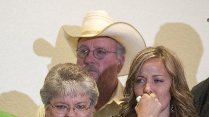 Christy Ivie, right, the wife of slain Border Patrol agent Nicolas Ivie, holds back tears as she stands with her father, Tracy Morris and  her mother DeAnn Morris, at a  news conference  Thursday, Oct. 4 , 2012,  at the Cochise College in Sierra Vista, Ariz. Nicholas Ivie was gunned down Tuesday, Oct 2, as he responded to a tripped sensor on the USA side of the border fence, near the small border town of Naco, Ariz. Ivie's  partner was also hit in gunfire during the exchange, but was released from a Tucson hospital on Wednesday. (AP Photo/Gary M. Williams)