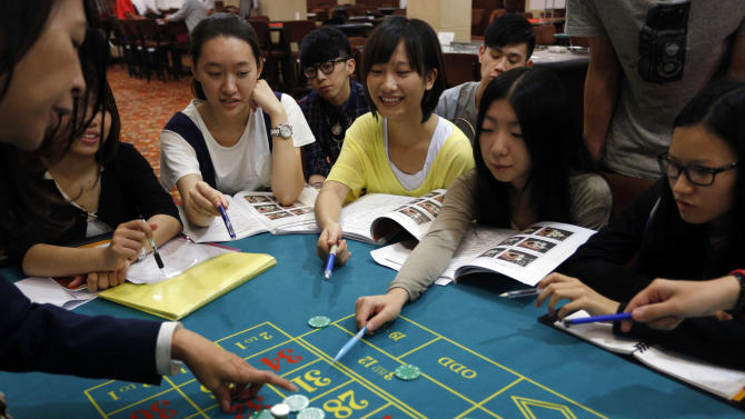 In this Nov. 25, 2012 photo, a gambling school students practice on a table in Macau, China. The students sitting around the roulette table are getting schooled on how to quickly calculate payoffs for the casino game by glancing at how the bets are placed. Elsewhere in the room, the biggest mock casino in Asia, other students are playing practice hands of blackjack or learning how to run a craps table. (AP Photo/Vincent Yu)