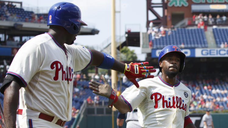 Philadelphia Phillies' Jimmy Rollins, right, celebrates his run with Ryan Howard, left, on the single by Chase Utley during the fifth inning of a baseball game against the Seattle Mariners, Wednesday, Aug. 20, 2014, in Philadelphia. (AP Photo/Chris Szagola)