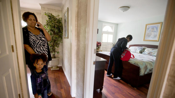 Retired Atlanta police Det. Jaqueline Barber,  right, sifts through bank forms as her daughter Yhonna Flowers, left, talks on the phone while standing with her daughter Choyce, 2, in their home Monday, Oct. 8, 2012, in Fayetteville, Ga. Less than a year after Occupy Atlanta members clashed with police in riot gear in a downtown park, they're now protesting alongside officers to help Barber avoid losing her home to foreclosure. Barber said she is under threat of eviction after her medical bills mounted, partly because of a diagnosis of multiple myeloma, a form of blood cell cancer. If she's evicted along with her daughter and four grandchildren, she expects that she will be homeless. (AP Photo/David Goldman)