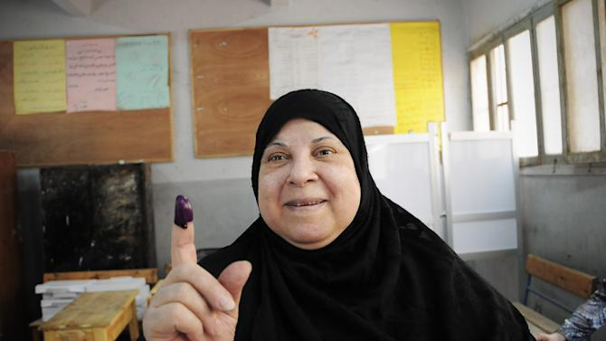An Egyptian woman shows her inked finger after casting her vote inside a polling station, in Giza, Egypt, Wednesday, May 23, 2012. More than 15 months after autocratic leader Hosni Mubarak's ouster, Egyptians streamed to polling stations Wednesday to freely choose a president for the first time in generations. (AP Photo/Mohammed Asad)