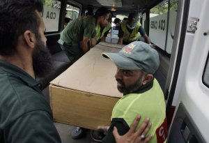 Pakistani rescue workers unload the casket of a foreign …