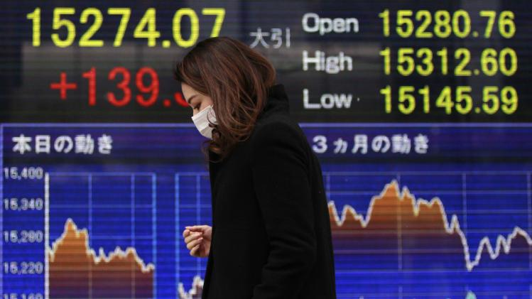 A pedestrian walks past an electronic board displaying the Japan's Nikkei average outside a brokerage in Tokyo