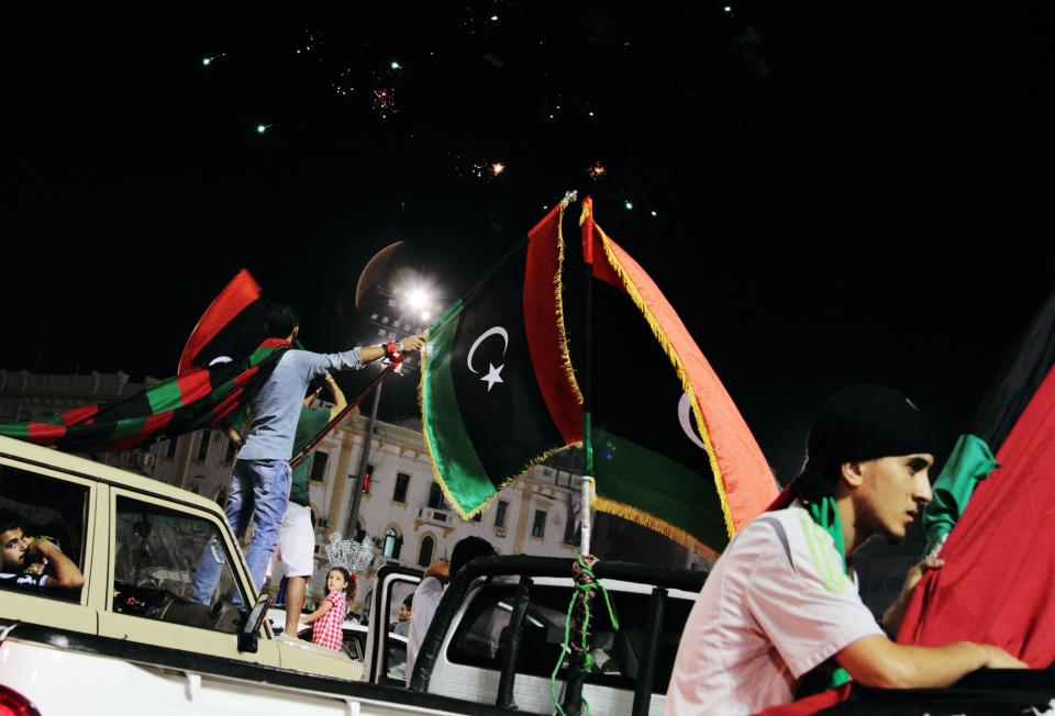 In this Saturday, Oct. 20, 2012 photo, Libyans wave their national flags as they celebrate the first anniversary of the capture and killing of former dictator Moammar Gadhafi at Martyrs Square in Tripoli, Libya. (AP Photo/Gaia Anderson)
