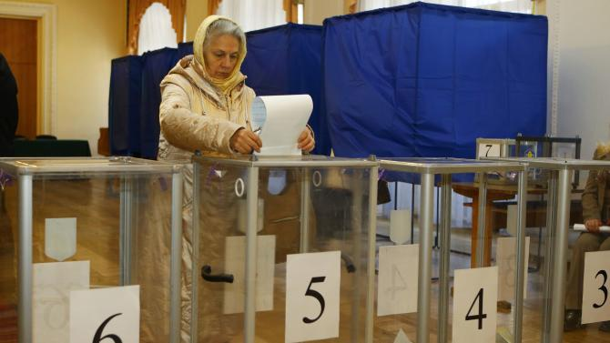 A woman casts a ballot during a parliamentary election at a polling station in Kiev
