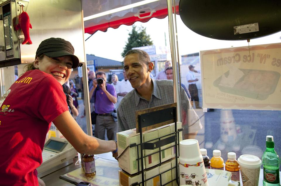"President Barack Obama visits Cookie Smith at the ""CinnieSmiths"" mini cinnamon roll stand at the Iowa State Fair, Monday, Aug. 13, 2012, in Des Moines, Iowa. The president is on a three-day campaign bus tour through Iowa. (AP Photo/Carolyn Kaster)"
