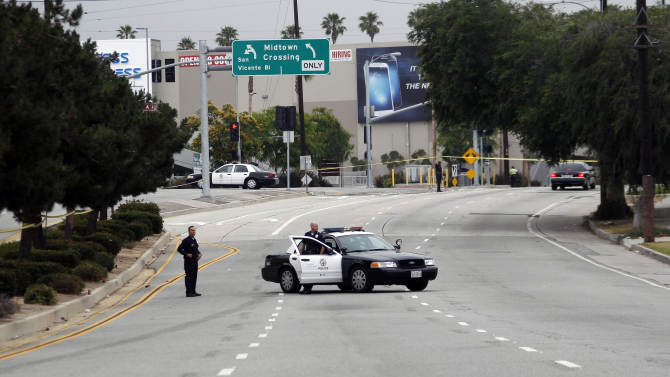 Los Angeles police officers close off a city street after two police officers were shot and wounded in an attack outside a police station in the Mid-City area of Los Angeles on Tuesday June 25, 2013. A black-clad gunman ambushed two detectives returning to a police station early Tuesday, but they received only minor injuries and were helping in the hunt for the attacker, police said. (AP Photo/Nick Ut)