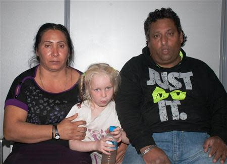 A Roma couple and a girl found living with them in central Greece, are seen in a handout photo distributed by the Greek police