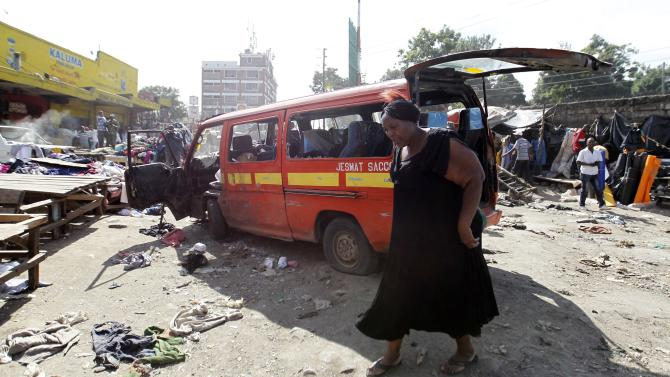 A woman walks near a damaged vehicle at the scene of a twin explosion at the Gikomba open-air market for second-hand clothes in Nairobi